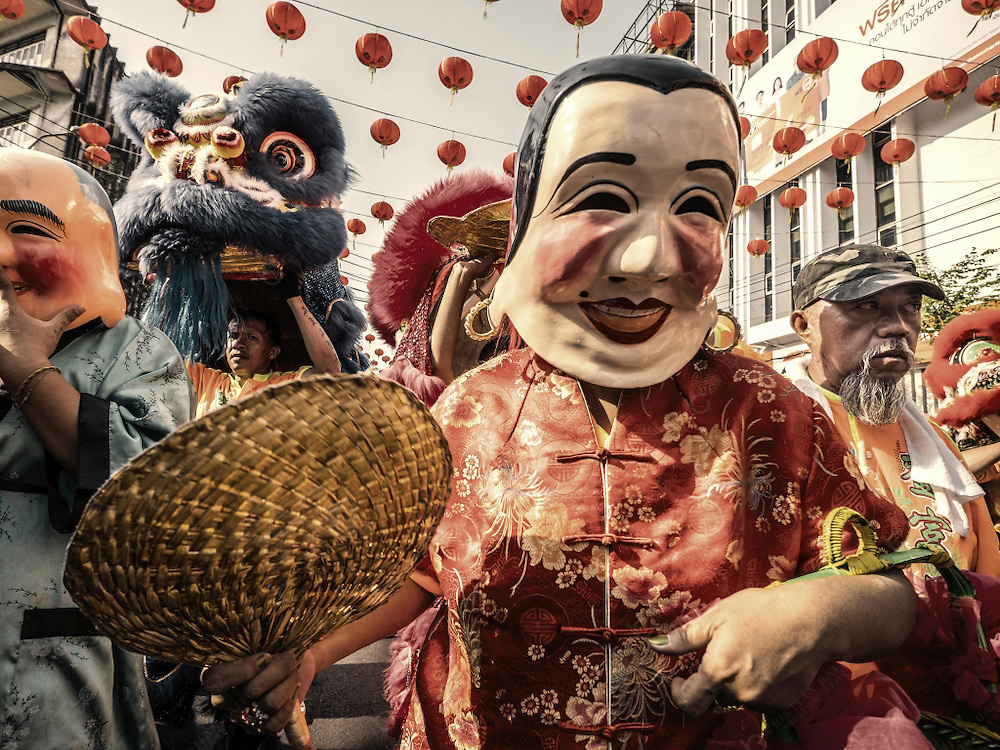 Lion dance and people with chinese masks at Yaowarat Road during the celebration of the Chinese New Year in Chinatown Bangkok Thailand