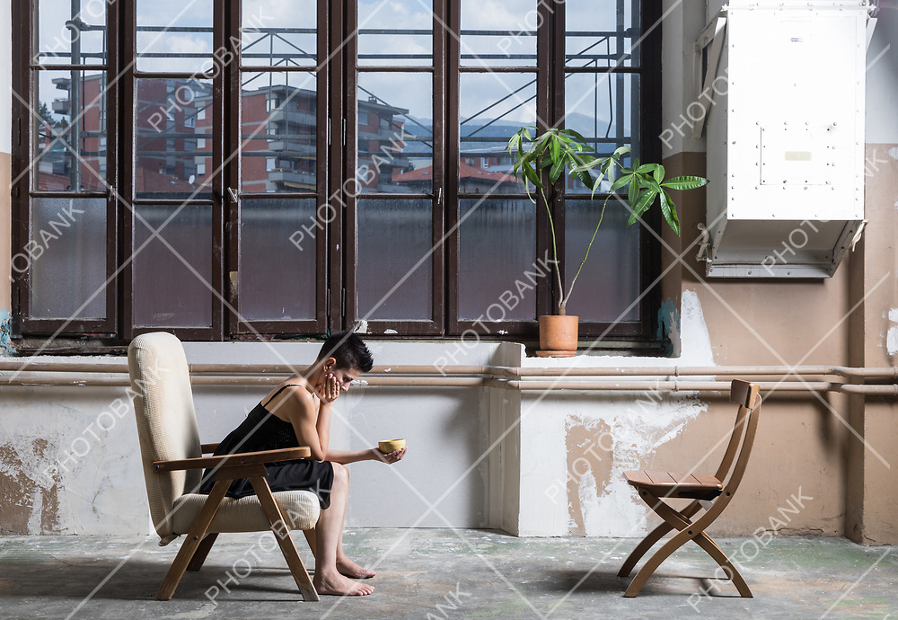 woman sitting on a profile armchair with a window behind