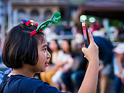 "23 DECEMBER 2018 - CHANTABURI, THAILAND: A girl wearing Christmas decorations takes a picture with her smart phone at the Cathedral of the Immaculate Conception's Christmas Fair in Chantaburi. Cathedral of the Immaculate Conception is holding its annual Christmas festival, this year called ""Sweet Christmas @ Chantaburi 2018"". The Cathedral is the largest Catholic church in Thailand and was founded more than 300 years ago by Vietnamese Catholics who settled in Thailand, then Siam.  PHOTO BY JACK KURTZ"