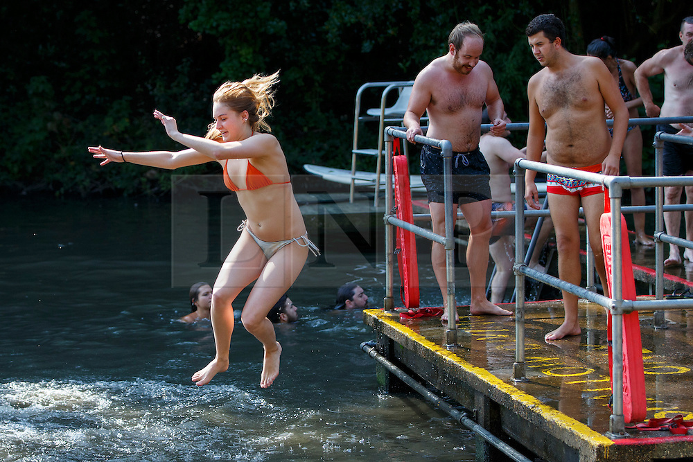 © Licensed to London News Pictures. 13/09/2016. London, UK. People jump into Hampstead Heath Mixed Bathing Pond in north London as temperatures hit 30C in London on Tuesday, 13 September 2016. Photo credit: Tolga Akmen/LNP