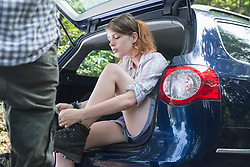 Young woman sitting in car boot and putting on her hiking shoes, Bavaria, Germany