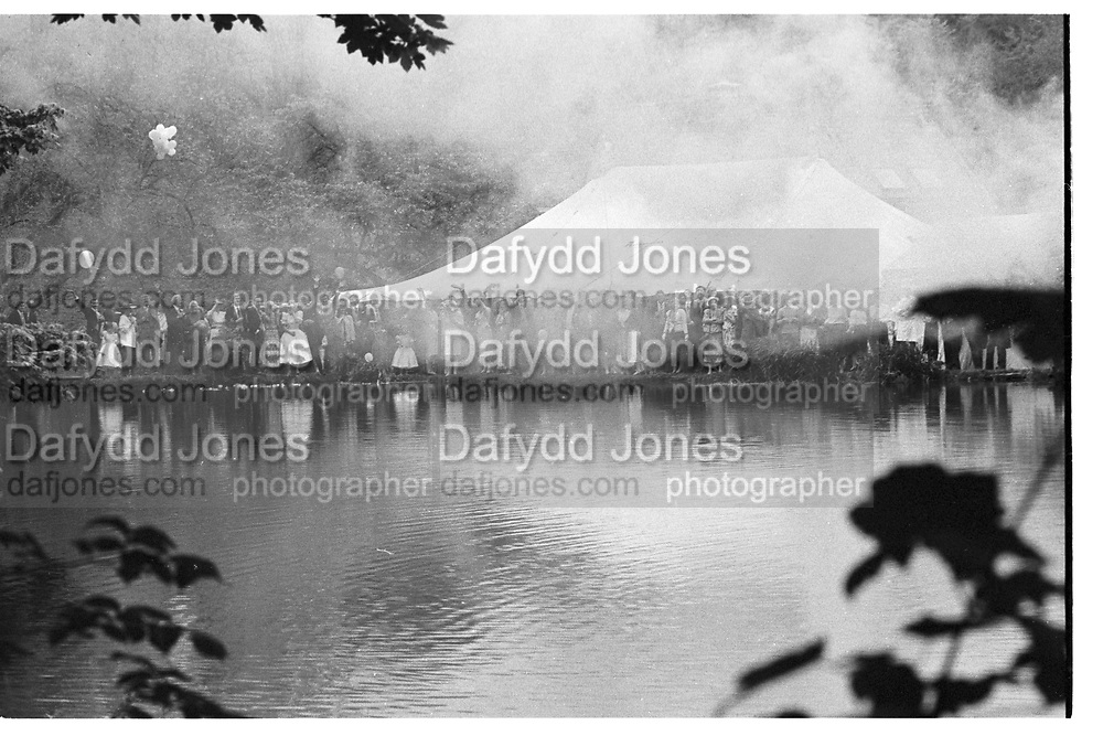 Guests seeing off bride and groom. Marriage Rupert Wielock/ Perinell Nevill, Bakers Mill, Frampton Mansell. 31 May 1986.<br /> <br /> SUPPLIED FOR ONE-TIME USE ONLY> DO NOT ARCHIVE. © Copyright Photograph by Dafydd Jones 248 Clapham Rd.  London SW90PZ Tel 020 7820 0771 www.dafjones.com