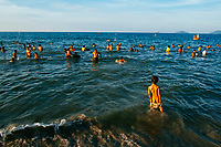 A young boy loses his bathing suit at An Bang beach in Hoi An, Vietnam. An Bang beach is particularly popular with locals in the late afternoon, when the beach and water get quite crowded.