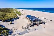 Nederland, Friesland, Vlieland; 19-09-2020; permanent strandpaviljoen 't Badhuys.<br /> Het paviljoen staat op palen waardoor wisselwerking tussen het zand van het strand (en de zee bij zeer hoog water) en de achterliggende duinen mogelijk is. Ontwerp H+N+S.<br /> <br /> luchtfoto (speciaal tarief);<br /> aerial photo (special fee required)<br /> copyright © 2020 foto/photo Siebe Swart
