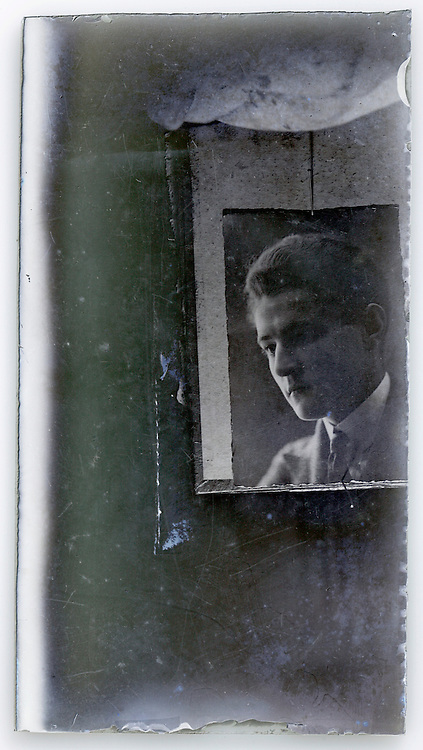 old glass plate with reproduction of portrait of young man which is held up with hand