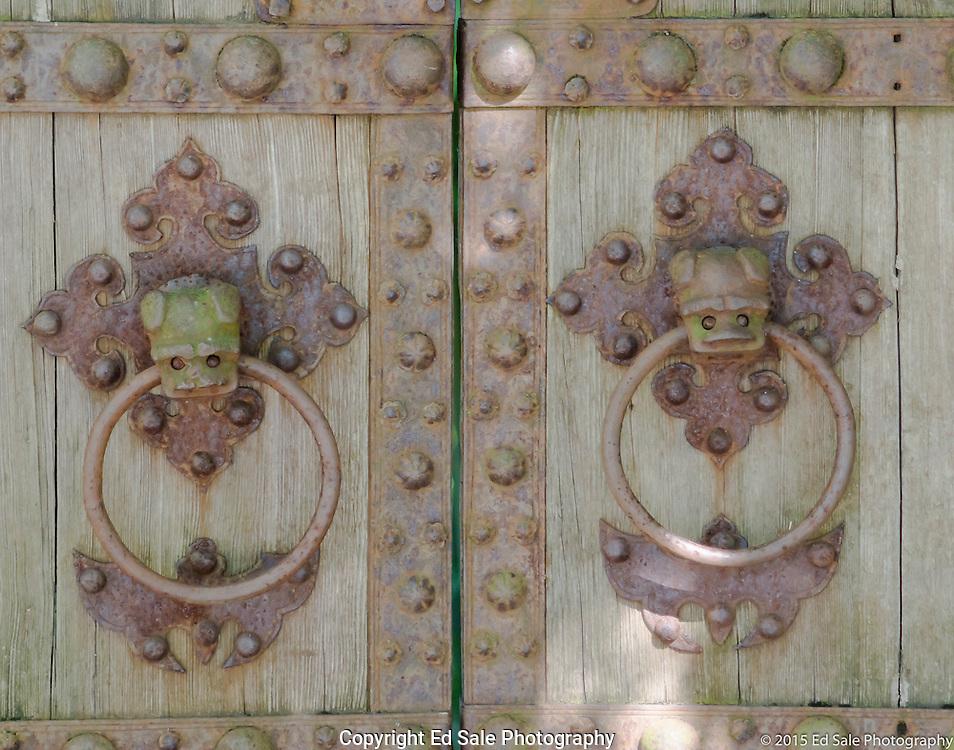 Weathered yard gate with bronze ring door knockers in Portland, Oregon