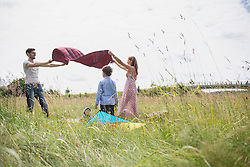 Family spreading picnic blanket on meadow in the countryside, Bavaria, Germany