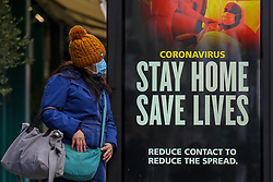 © Licensed to London News Pictures. 10/01/2021. London, UK. A woman wearing a protective face covering looks at the Government's 'Stay Home, Save Lives' Covid-19 publicity campaign poster in north London, as the number of cases of the mutated variant of the SARS-Cov-2 virus continues to spread around the country. The message in the advertising campaign poster asks people to 'reduce contact to reduce the spread'. Almost 60,000 new cases of coronavirus were reported in the UK on Saturday 9 January 2021 and the number of deaths after a positive test passed 80,000, since the pandemic began. Photo credit: Dinendra Haria/LNP