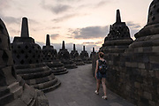 An European female tourist walking at Borobudur Temple on the 24th October 2019 in Java in Indonesia. Borobudur is a 9th-century Mahayana Buddhist temple in Magelang Regency. It's the worlds largest Buddhist temple, consisting of nine stacked platforms, six square and three circular, topped by a central dome.