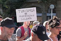 "@Licensed to London News Pictures 17/08/17. San Sebastian, Basque Country, Spain. Protestors leading an anti-tourism march today through the crowded streets of the Basque town of San Sebastian in Spain. The banner translation from Basque is "" Tourism = miserable pay"". Following on from similar demonstrations in Barcelona protestors in San Sebastian are protesting against the  over-tourism of their country.  Photo credit: Manu Palomeque/LNP"