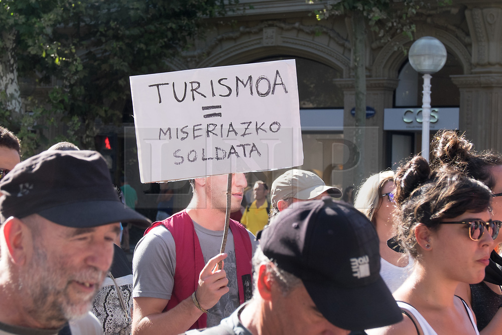"""@Licensed to London News Pictures 17/08/17. San Sebastian, Basque Country, Spain. Protestors leading an anti-tourism march today through the crowded streets of the Basque town of San Sebastian in Spain. The banner translation from Basque is """" Tourism = miserable pay"""". Following on from similar demonstrations in Barcelona protestors in San Sebastian are protesting against the  over-tourism of their country.  Photo credit: Manu Palomeque/LNP"""