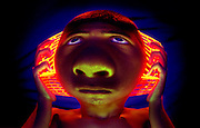 Young boy holding glowing earphone to his head.Black light