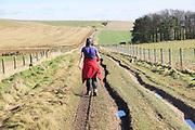 Woman walking on footpath Roman road to Beckhampton, Cherhill Downs, Wiltshire, England, UK