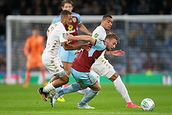 Leeds United's Kemar Roofe (left) and Burnley's Charlie Taylor battle for the ball during the Carabao Cup, third round match at Turf Moor, Burnley.