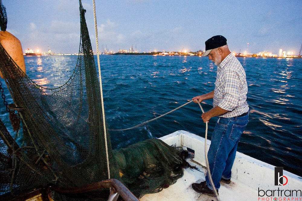 KEVIN BARTRAM/The Daily News.Jerome Kunz lowers his net into the Galveston Ship Channel early Wednesday morning, July 12, 2006. Kunz shrimps in the channel aboard his boat the St. Vincent.