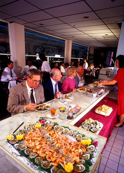 Stock photo of a group of older people eating at a bar area of a restaurant
