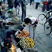 NEPAL, Kathmandu.  Young street vendor warms himself while selling fruit near Durbar Square on a chilly autumn morning.