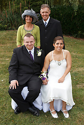Bride who has cerebral palsy, with groom and bride's family at wedding ceremony.