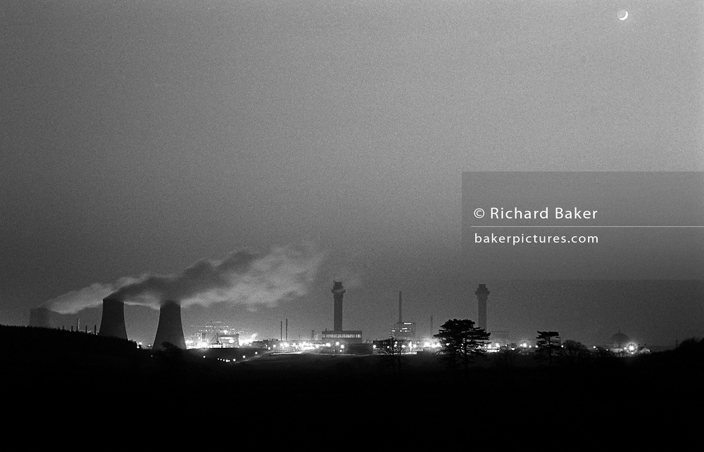 The industrial Sellafield nuclear reprocessing glows on the skyline in the darkness of the Cumbrian countryside