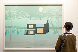 "© Licensed to London News Pictures. 22/04/2015. Piccadilly, London. A woman looks at Tom Hammick's ""Outskirts"" at the press review at the 30th London Original Print Fair, Europe's largest works–on–paper event, which takes place at the Royal Academy of Arts from 23 to 26 April 2015.  On display are works from all periods of printmaking, from the earliest woodcuts of Dürer, to the latest editions by contemporary masters. Photo credit : Stephen Chung/LNP"