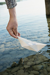 Close up young man launching paper boat water