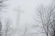 Mont Royal Cross / Croix du Mont royal in the mist and fog in Snow covered Mont Royal Park in Winter, Parc du Mont Royal, Montreal, Quebec, Canada