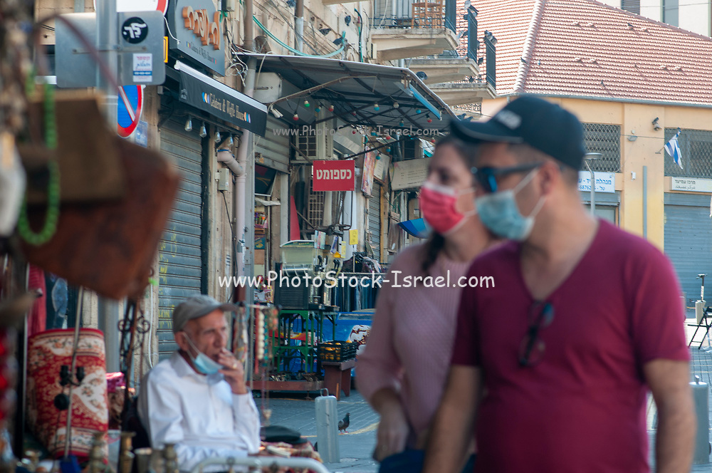 Tourism under COVID-19. a couple with face masks is at leisure at the Jaffa flea market. with a bit of lax regulations between lockdowns Israelis attempt to bring back a bit of normality to their lives by visiting scarcely populated and operational landmarks and places of interest [ most shops and all stall in the flea market are currently closed]