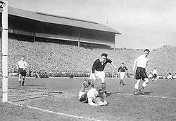 Willie Waddell, Scotland's inside right, races in but England goalkeeper Bert Williams has the ball tucked safely away during the international match at Hampden Park.
