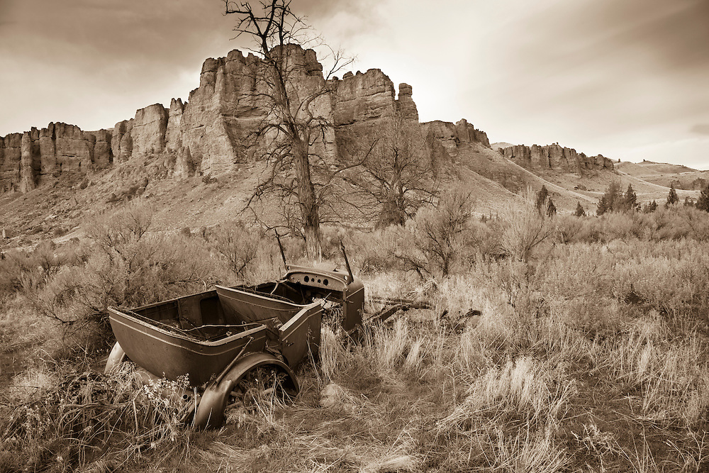 The skeleton of an ancient car, with wooden spoked wheels, lies partly buried in the soil of central Oregon's high desert.