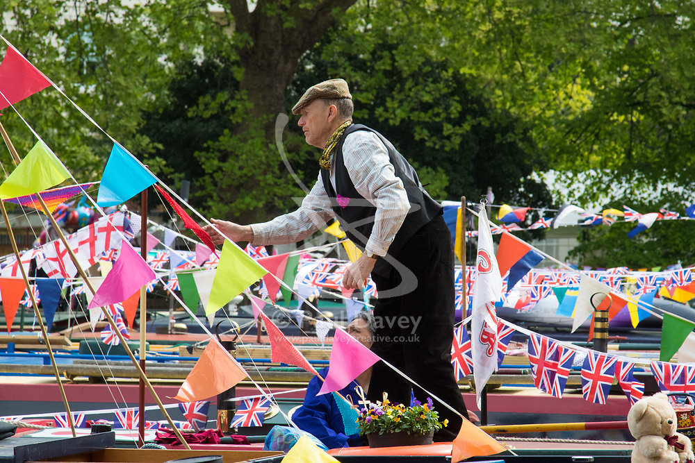 Little Venice, London, April 30th 2017. Narrowboaters from all over the uK gather for the annual Canalway Cavalcade, held on the May Day Bank holiday weekend, organised by the Inland Waterways Association, where boaters get the chance to display their immaculately prepared and brightly painted craft as well as compete in various manoeuvring tests. PICTURED: A narrow boater adjust his bunting.<br /> Credit: ©Paul Davey<br /> To licence contact: <br /> Mobile: +44 (0) 7966 016 296<br /> Email: paul@pauldaveycreative.co.uk<br /> Twitter: @pauldaveycreate