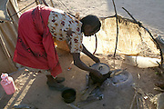A young refugee mother prepares to cook a meal of aiysh (the thick porridge that this refugee family eats three times a day), in the makeshift kitchen area outside of her United Nations-issued tent at Breidjing Refugee Camp in eastern Chad. (Supporting image from the project Hungry Planet: What the World Eats.)