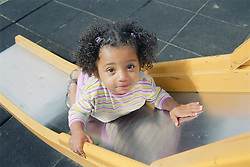 Young girl trying to climb up playground slide,