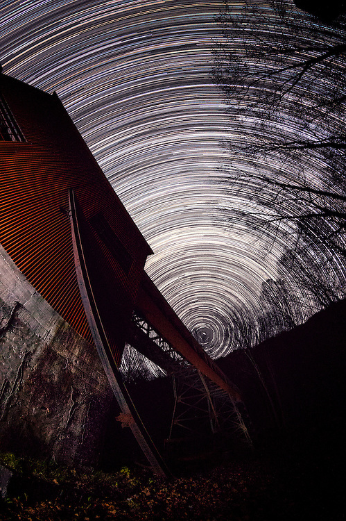 4 hours of the earth's rotation are captured by the star trails streaking across the sky, with Polaris hanging just above the tipple's conveyer belt at the abandoned mining site in Nuttallburg, now owned by the National Park Service and part of the New River Gorge in West Virginia, USA.