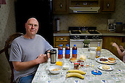 Kelvin Lester, a floor supervisor at a meat processing company with his typical day's worth of food at his kitchen table in Grand Meadow, Minnesota. (From the book What I Eat: Around the World in 80 Diets.) The caloric value of his typical day's worth of food in June was 2,600 kcals. He is 44 years of age; 5 feet, 11 inches tall; and 195 pounds. The hands on the right belong to Kiara, his four-year-old adopted daughter. Several times a week, hamburger patties that he purchases with an employee discount wind up on his dinner table, and then go into his lunch box, along with his wife's homemade potato salad. With more than 20 years of experience grinding beef at the Rochester Meat Company, Kelvin says he always grills hamburgers?no matter who has ground them?until they are well-done, because any contamination is most easily rendered harmless by thorough cooking, meaning cooking them to an internal temperature of at least 160 degrees Fahrenheit. MODEL RELEASED.