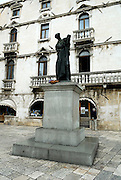 Statue of Marko Marulic, famed Croatian poet, humanist and writer, with Milesi Palace in background. Brace Radica Square (trg Brace Radica) also known as Vocni trg (Fruit square), Split, Croatia
