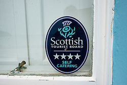 Sign in guest house window in Scottish village showing it is a self catering guest house and part of Scottish Tourist board scheme