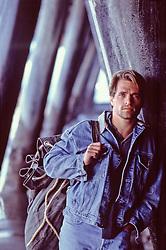 sexy man holding a sack under a pier