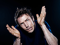 studio portrait on black background of a funny expressive caucasian man puckering scared fear