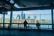 Silhouetted rail travellers look out of the wide glass windows of Blackfriars Station that stretches across the river Thames, and which overlooks a panaorama of the City of London, the capitals financial district, on 26th February 2021, in London, England.