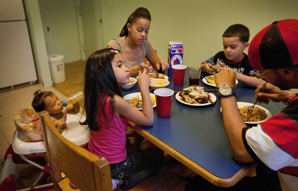 Left to right, Nylah Jamie, 1, Alexsia Jaime, 5, mother Coraly Rivera, 24, Anthony Torres, 6, and father Pablo Jaime, 28, share dinner in their temporary home inside a shelter in Harlem, New York, N.Y., Sept. 10, 2011.