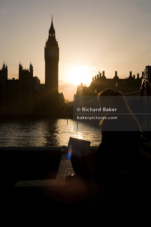Young lady reads book during peaceful moment on Thames River opposite Big Ben and Parliament at sunset.