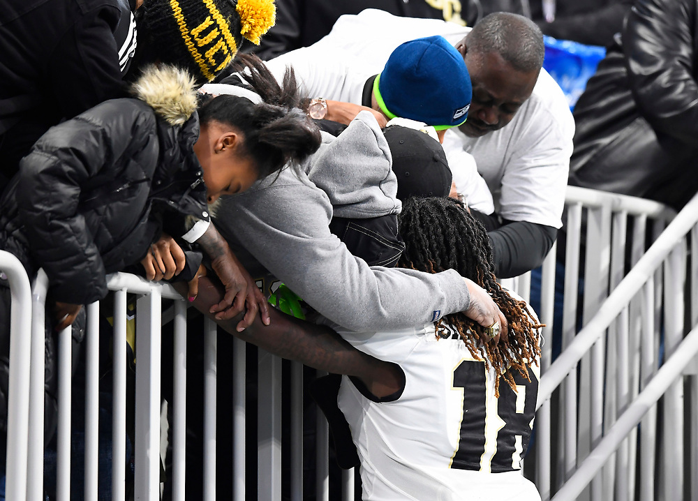 UCF Knights linebacker Shaquem Griffin (18) hugs his family before the Chick-fil-A Peach Bowl NCAA college football game January 1, 2018, in Atlanta. (David Tulis via Abell Images for Chick-fil-A Peach Bowl)