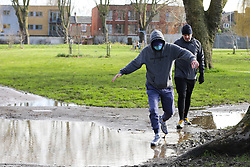 © Licensed to London News Pictures. 05/02/2021. London, UK. Men avoid walking through the puddle of water in Chestnuts Park, north London. Part of the footpath in the park is flooded following heavy overnight rain in London. According to the Met Office, snow is forecast for the weekend.  Photo credit: Dinendra Haria/LNP