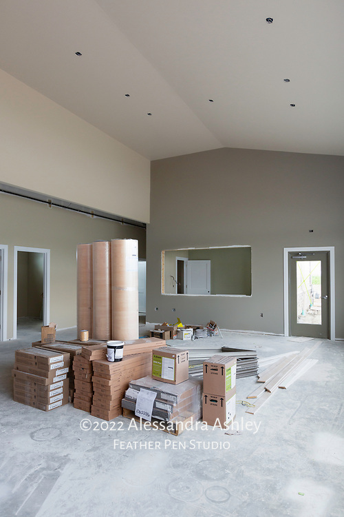 Interior wall painting begins at building site of new physical therapy and wellness center. Back wall of gymnasium is pictured in gray tone, with window view into staff room (sage green). Flooring supplies are shown on the gym floor.