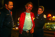 Paramedics assist a bloodied man under the influence of alcohol, picked up by Atlanta police after a street altercation.