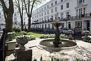 On a fine spring day, we see the ornate fountain, ornamental central garden and beyond, the grand terraced properties of Wellington Square, SW3 in the borough of Kensington & Chelsea, London England. The pristine houses are all identically painted white, their perfect iron railings all black as are their heavy gloss-painted doors. Wellington Square is off the King's Road Chelsea and was built around 1830: Named after the 1st Duke of Wellington (the heroic Commander-in-Chief of the British Army - most famously at Waterloo in 1815 - then a Tory politician and in 1834, temporary Prime Minister).