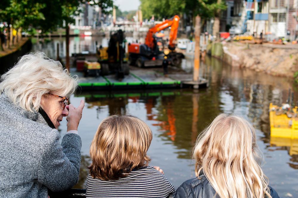 Een oma kijkt met twee kleinkinderen naar de ingestorte kademuur. In Utrecht is aan de Bemuurde Weerd een deel van een historische kademuur ingestort. De oorzaak is mogelijk dat door de heftige regenval eerder in de week een boom is omgevallen. Op dit moment wordt een nooddamwand geplaatst.<br /> <br /> In Utrecht at the Bemuurde Weerd a part of a historic quay collapsed . The possible cause is that the heavy rainfall earlier in the week a tree has fallen. At this moment emergency piling takes place.