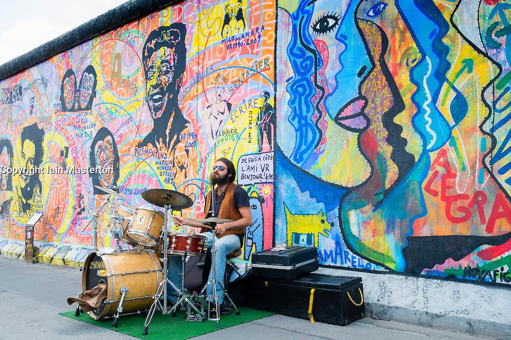Musician busking on street beside Berlin Wall at the East Side Gallery in Berlin Germany