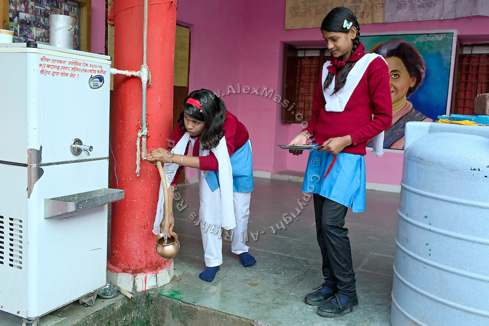 Ritu Gaur, 13, (left) is taking a pot of drinking water inside the Jamoniya Tank Girls Hostel, near Sehore, Madhya Pradesh, India, where the Unicef India Sport For Development Project has started in 2012. Covering 313 state-run girls' hostels and 207 mixed hostels in Madhya Pradesh, the project ensures that children from Scheduled Tribes (ST) and others amongst the poorest people in India, can easily access education and be introduced to sports. Field workers from Unicef also oversee their nutrition and monitor the overall conditions of each pupil.