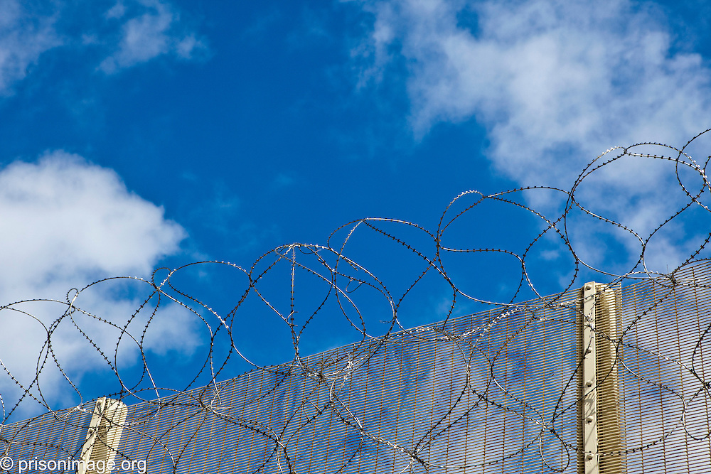 The barbed wire on top of the perimeter fence at HMP & YOI Littlehey. Littlehey is a purpose build category C prison.